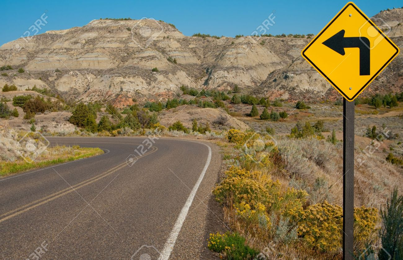15637500-left-turn-sign-a-road-sign-warns-of-a-sharp-left-turn-on-a-narrow-road-through-theodo...jpg